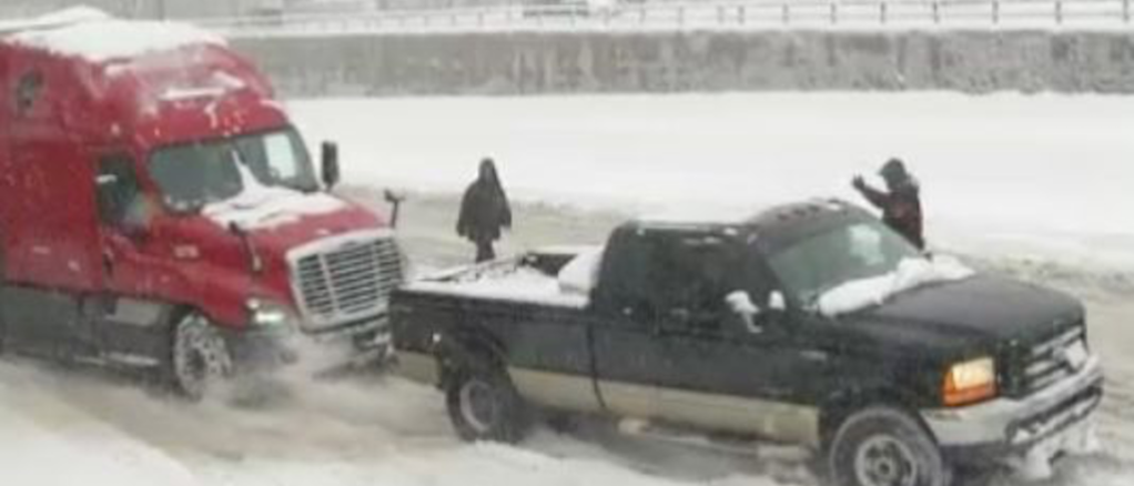 Watch a hero in a pickup truck pull a 50,000 lb  semi out of